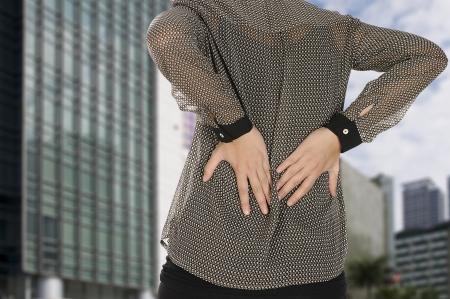 Mujer de negocios tener dolor de espalda con el fondo del edificio de oficinas Foto de archivo