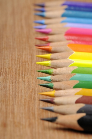 Colour pencils shot on wooden background close up photo