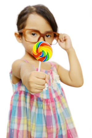 Cute little girl wearing glasses eating her lollipop isolated over white background photo