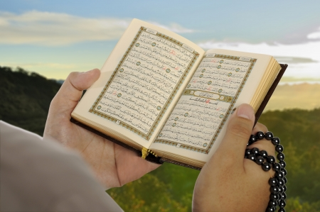 Young man reading the Holy Koran in the morning. This is eid mubarak concept photo