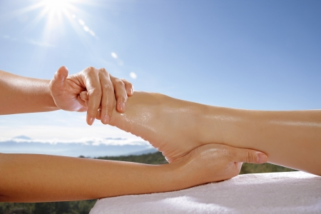 Woman legs get foot massage with blue sky background. This is spa concept Stock Photo