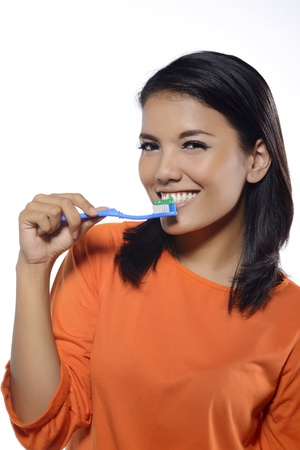 Portrait of pretty asian smiling woman isolated on white background brushing her teeth photo