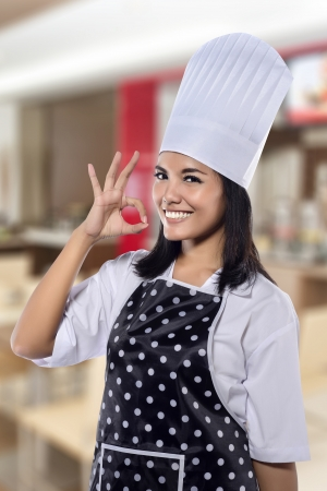 Portrait of beautiful pretty woman chef with restaurant background photo