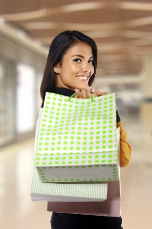 Portrait of young happy woman with shopping bags, with mall background photo