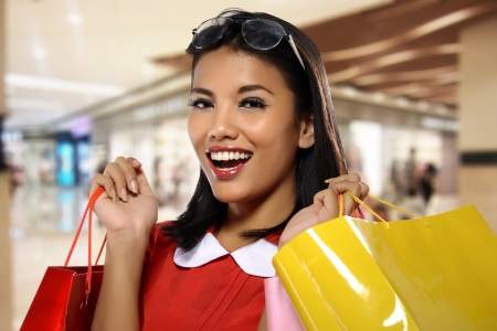 Portrait of young happy woman with shopping bags, with mall background Stock Photo - 21494205