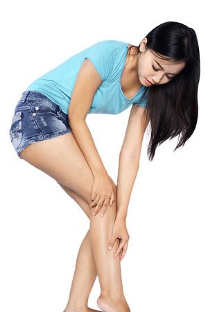 Injury. Woman holding on leg isolatec over white background photo