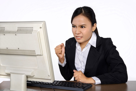 A young businesswoman is looking stressed as she works at her computer. Isolated over white background photo