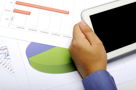 Business man holding tablet. Analyze sales and profit. You can put your design on the screen photo