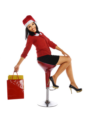 Beautiful young woman with christmas present sittng on chair isolated on white background. photo