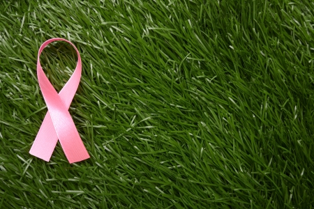 Pink ribbon on green grass. Breast cancer awareness concept. You can put your design here Stock Photo