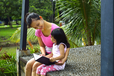 Mother and daughter reading book on the park photo