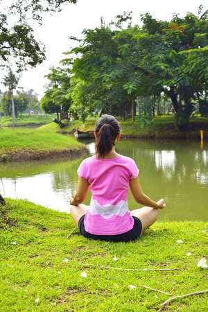 An attractive young woman doing a yoga pose near the lake photo