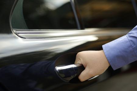 Man hand on handle is opening a car door
