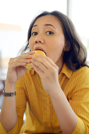 Pretty Young Woman Eating Burger Enjoying Break Lunch In Cafe photo