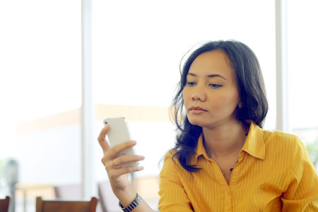 Young Pretty Attractive Asian Woman Texting Her Smartphone With Serious Face Expression In The Morning At Cafe photo
