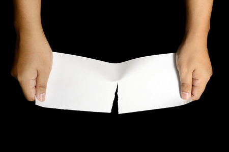 Hand tearing white paper isolated over white background photo