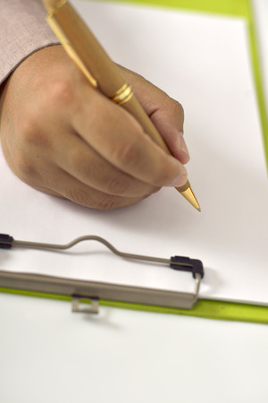 Man writing on blank paper on clipboard. You can put your design on it photo