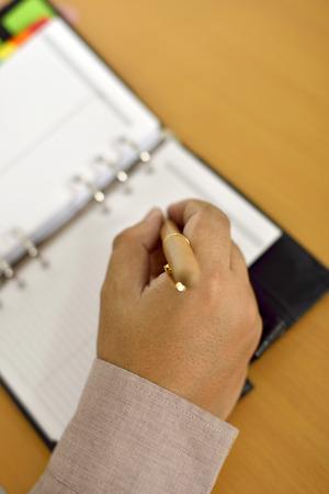 Business man writing on agenda over office desk photo