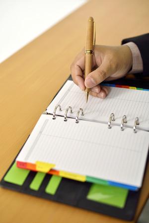Business Man writing on agenda on the desk photo