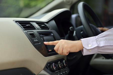 estereo: Hombre Encienda la radio mientras se conduce. Imagen del concepto de Automoci�n