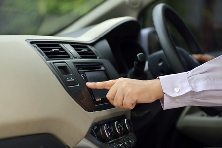 dash: Man Turn On Radio While Driving. Automotive concept image Stock Photo