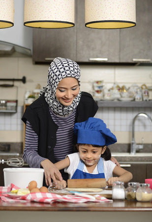 Moslem woman wearing hijab, teaching her daughter make halal food