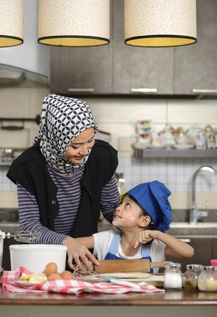 asian cooking: Moslem woman wearing hijab, teaching her daughter make halal food
