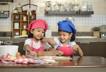 niños cocinando: Dos niñas hacer la pizza en la cocina