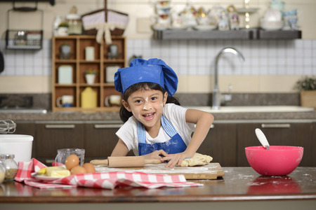 little dough: Little asian girl making dough in the kitchen Stock Photo