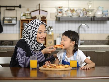 familia cenando: Madre e hija comiendo pizza en el comedor