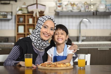 Moeder en dochter het eten van pizza in de eetkamer Stockfoto - 38720146