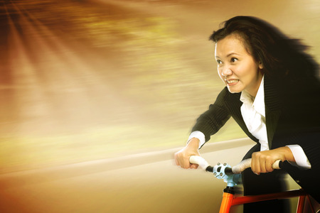 Businesswoman in a rush riding a bicycle in a sunny day showing motion movement to reach a goal photo