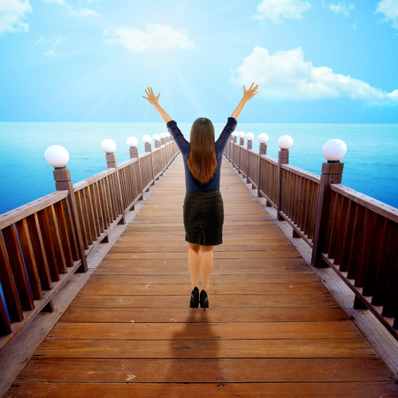 raise hand: Back view of woman raise hand up on pier. Conceptual of working freedom