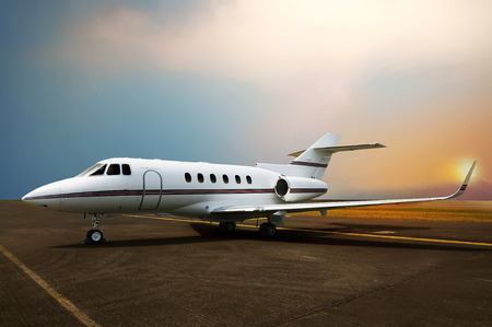 Private jet airplane parking at the airport. With sunset background