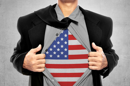 Business man tears open his shirt with american flag in a super hero fashion getting ready to save the day. 4th of July concept photo
