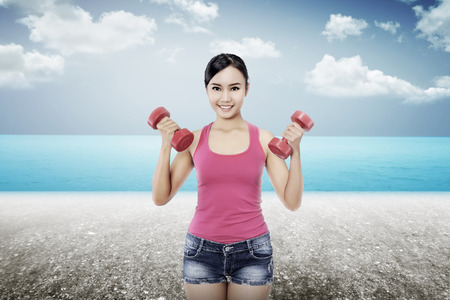 dumbell: Woman exercise with dumbell on the beach concept Stock Photo