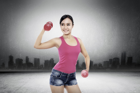dumbell: Woman exercise with dumbell with cityscape concept