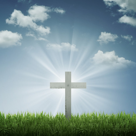 the passion of christ: Christian cross with blue sky and cloud background. With ray of light effect