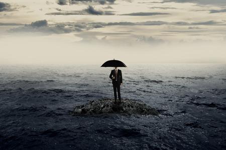 estado del tiempo: Hombre que sostiene el paraguas de pie sobre la roca en el tiempo withbad mar. Concepto de recesi�n de negocios
