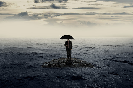 success risk: Man holding umbrella standing on the rock on the sea withbad weather. Business recession concept Stock Photo