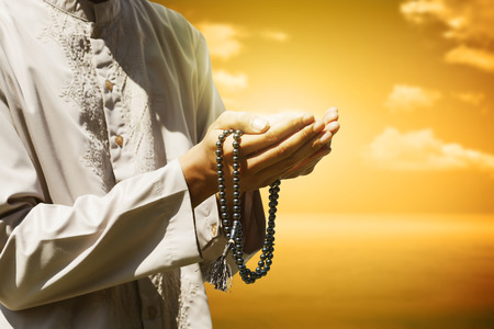 islamic pray: Hand of muslim people praying with sunset background Stock Photo
