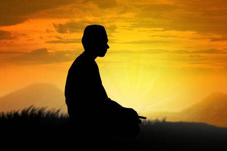 orando: Silueta del hombre musulmán orando con el atardecer de fondo
