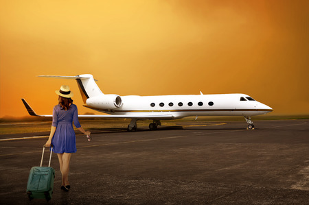 Traveler woman with walk with suitcase into private jet airplane. Travel concept