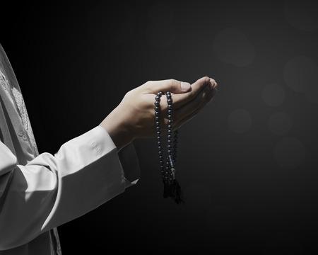 orando: Mano de las personas musulmanas con orando gesto sobre fondo oscuro