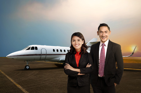 Business man and woman smiling in front of private jet. Business travel concept photo