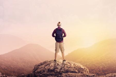 backpack: Backpacker joven que disfruta de una vista al valle desde la cima de una montaña Foto de archivo
