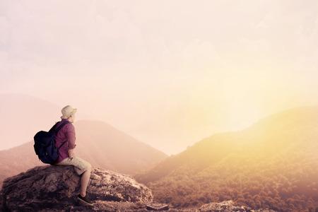 渓谷の景色を楽しむ若いバックパッカー 山の頂上から 写真素材