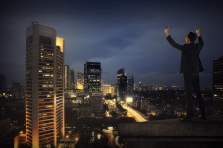 city light: Business man shout on the building rooftop. Success in business concept