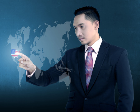 virtual world: Asian business man touch USA on virtual world. Business expansion to USA