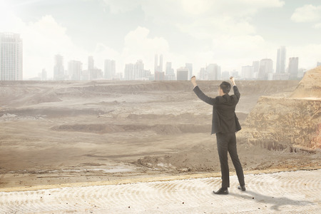Asian business man looking at the destroyed city. Business corruption conceptual